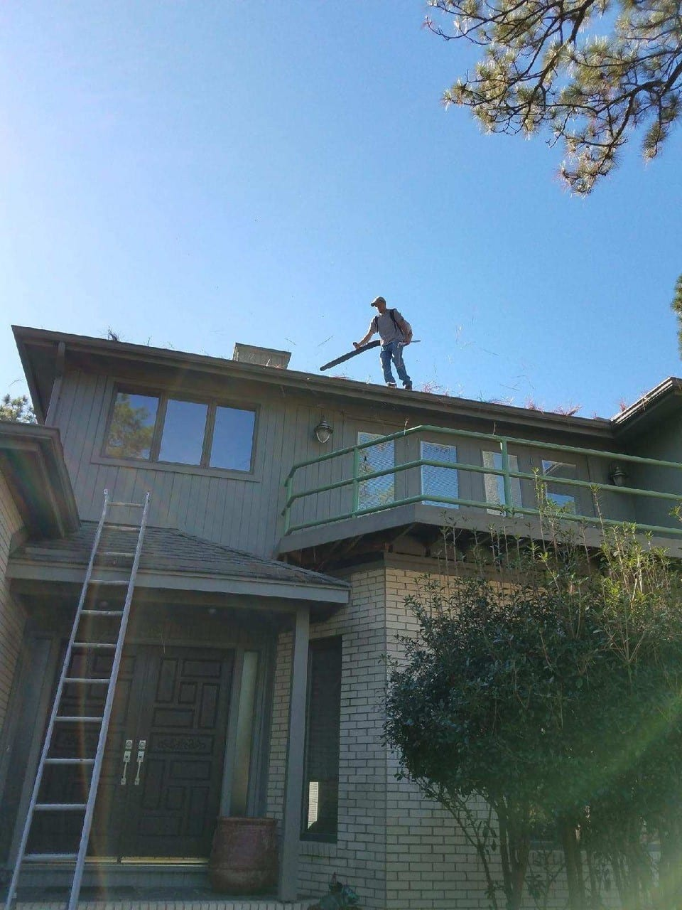 man on roof cleaning gutters